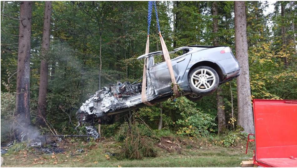 Doutnající elektromobil Tesla po nehodě na Rakouské silnici při převozu do nádrže s vodou k definitivnímu uhašení, foto BFI Bernhard Geisler.