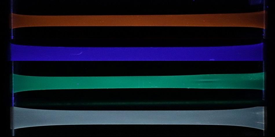 Zářící napnuté polyuretanové pásky se zabudovanými rotaxanovými luminofory. Ve spodním pásku najdeme všechny tři luminofory záříci modře, zeleně a oranžově, obr.Hokkaidská univerzita.