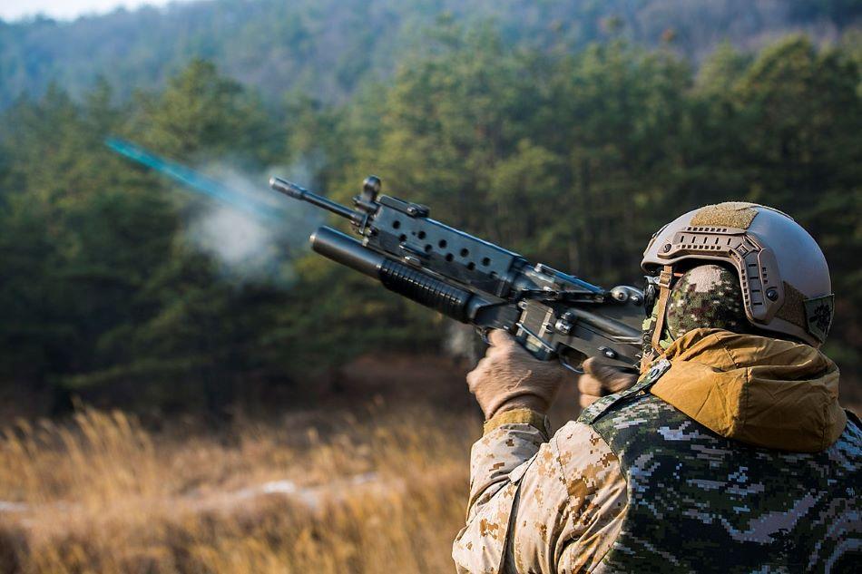 Desátník (Corporal) americké námořní pěchoty Richard J. Bennaugh  pálí  z jihokorejského  40 mm granátometu Daewoo K201 pod útočnou puškou, foto Cpl. Tyler Giguere/Public domain, https://commons.wikimedia.org/wiki/File:US_Marines_operate_ROK_weapons_150205-M-RZ020-004.jpg .