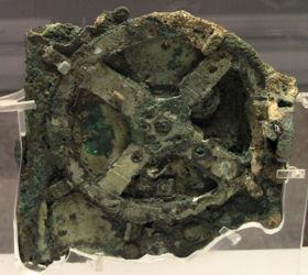 Hlavní fragment mechanismu z Antikythery, zvaný fragment A. Kromě něj existují ještě 2 menší a asi 80 zlomků.  GNU Free Documentation License 1.2, Wikimedia Commons, Athénské národní archeologické muzeum.