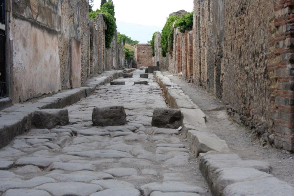 Ulice v Pompejích. Kamenné bloky sloužily chodcům k přecházení přes vozovku, která sloužila zároveň jako drenáž a posila kanalizace, Alago [Public domain].