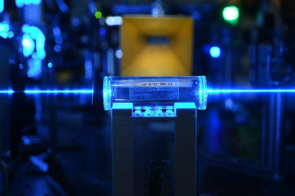 Uspořádání experimentu s Rydbergovými atomy. Ve skleněné nádobce vpředu laserový paprsek excituje atomy do Rydbergova stavu. Elektromagnetické pole ze zlaté antény v pozadí je rozkmitá. Informaci o frekvenci vepíší Rydbergovy atomy zpět do laserového paprsku.
