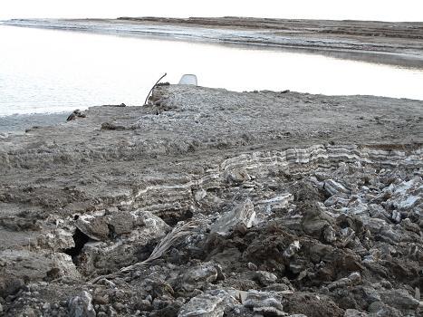 Usazeniny na břehu Mrtvého moře. Bílé vrstvy jsou tvořeny vykrystalovanými ve vodě rozpustnými solemi.